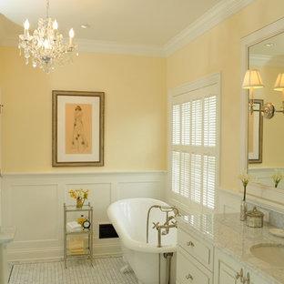 На фото: ванные комнаты среднего размера в классическом стиле с врезной раковиной, фасадами с выступающей филенкой, белыми фасадами, мраморной столешницей, ванной на ножках, раздельным унитазом, белой плиткой, каменной плиткой, желтыми стенами и мраморным полом