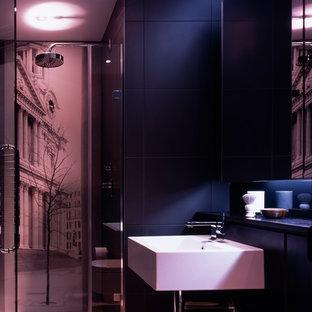 Ispirazione per una stanza da bagno con doccia moderna di medie dimensioni con ante di vetro, ante in legno bruno, doccia alcova, WC sospeso, piastrelle nere, piastrelle in gres porcellanato, pareti nere, pavimento in gres porcellanato, lavabo sospeso e top in marmo