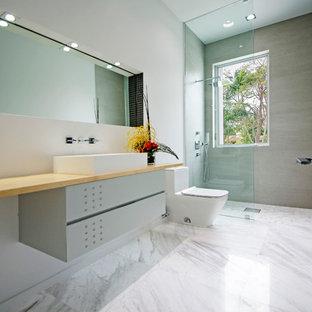 Immagine di una stanza da bagno con doccia moderna di medie dimensioni con ante grigie, doccia aperta, WC monopezzo, piastrelle grigie, pareti bianche, top in legno, lavabo a bacinella, pavimento in marmo, ante lisce e doccia aperta