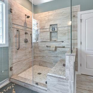 Exemple d'une salle de bain principale bord de mer avec un placard avec porte à panneau surélevé, des portes de placard en bois sombre, un WC séparé, un carrelage beige, des carreaux de porcelaine, un mur bleu, un sol en carrelage de porcelaine, un lavabo encastré, un plan de toilette en granite, un sol beige, une cabine de douche à porte battante et un plan de toilette beige.