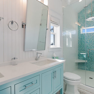 Example of a mid-sized beach style master glass tile vinyl floor bathroom design in Other with shaker cabinets, blue cabinets, a two-piece toilet, an undermount sink and limestone countertops