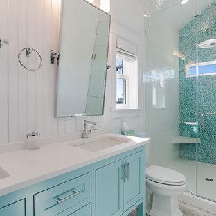 Foto de cuarto de baño principal, marinero, de tamaño medio, con armarios estilo shaker, puertas de armario azules, sanitario de dos piezas, baldosas y/o azulejos de vidrio, suelo vinílico, lavabo bajoencimera y encimera de piedra caliza