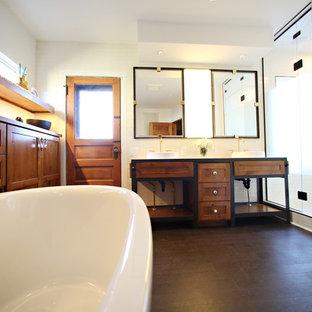 Modelo de cuarto de baño principal, industrial, grande, con lavabo encastrado, armarios con paneles empotrados, puertas de armario de madera oscura, encimera de cemento, bañera exenta, ducha empotrada, sanitario de una pieza, baldosas y/o azulejos blancos, baldosas y/o azulejos de porcelana, paredes blancas y suelo de corcho