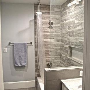 Idee per una stanza da bagno classica di medie dimensioni con ante lisce, ante gialle, vasca ad alcova, vasca/doccia, piastrelle beige, piastrelle marroni, piastrelle in gres porcellanato, pareti grigie, pavimento in gres porcellanato, lavabo sottopiano e top in marmo
