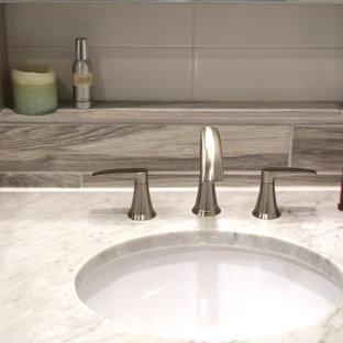 Ispirazione per una stanza da bagno tradizionale di medie dimensioni con ante lisce, ante gialle, vasca ad alcova, vasca/doccia, piastrelle beige, piastrelle marroni, piastrelle in gres porcellanato, pareti grigie, pavimento in gres porcellanato, lavabo sottopiano e top in marmo