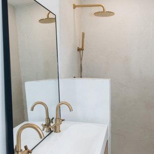 Inredning av ett retro litet vit vitt en-suite badrum, med släta luckor, skåp i ljust trä, en dusch i en alkov, vita väggar, cementgolv, bänkskiva i akrylsten och blått golv