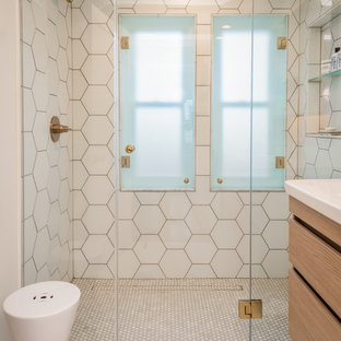 Walk-in shower - small contemporary master white tile and ceramic tile marble floor and white floor walk-in shower idea in Milwaukee with flat-panel cabinets, light wood cabinets, a wall-mount toilet, white walls, an integrated sink, solid surface countertops, a hinged shower door and white countertops