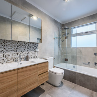Inspiration for a mid-sized contemporary bathroom in Melbourne with a drop-in tub, a shower/bathtub combo, multi-coloured tile, grey walls, ceramic floors, marble benchtops, grey floor, white benchtops, flat-panel cabinets, medium wood cabinets, mosaic tile, an integrated sink and an open shower.