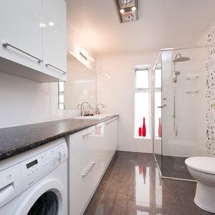 Diseño de cuarto de baño con ducha, moderno, pequeño, con puertas de armario blancas, ducha empotrada, sanitario de una pieza, baldosas y/o azulejos blancos, paredes blancas y lavabo encastrado