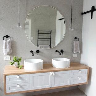 Immagine di una stanza da bagno padronale moderna con ante in stile shaker, ante in legno chiaro, piastrelle grigie, piastrelle di cemento, pareti grigie, pavimento in cementine, lavabo a consolle e top in legno