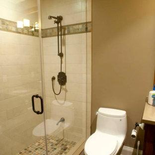 Diseño de cuarto de baño con ducha, de estilo americano, pequeño, con armarios estilo shaker, puertas de armario de madera en tonos medios, ducha esquinera, sanitario de una pieza, paredes beige, suelo de pizarra, lavabo bajoencimera y encimera de acrílico