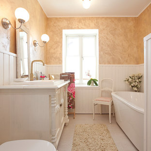 Trendy freestanding bathtub photo in Other with a drop-in sink, furniture-like cabinets, white cabinets and a two-piece toilet