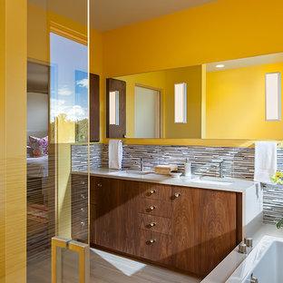 Esempio di una stanza da bagno padronale design di medie dimensioni con ante lisce, ante in legno scuro, vasca da incasso, doccia ad angolo, piastrelle a listelli, pareti gialle, pavimento in gres porcellanato, lavabo sottopiano, top in quarzite e piastrelle multicolore
