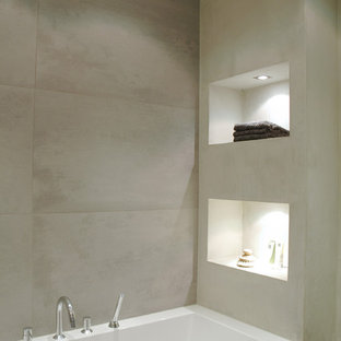 Design ideas for a modern bathroom in Amsterdam with a built-in bath and grey tiles.