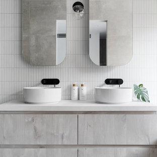 Inspiration för mellanstora moderna vitt en-suite badrum, med vit kakel, keramikplattor, vita väggar, ett fristående handfat, släta luckor, klinkergolv i porslin, bänkskiva i kvarts, grått golv och grå skåp