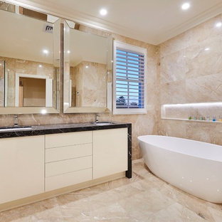 Inspiration for a contemporary master bathroom in Melbourne with flat-panel cabinets, white cabinets, a freestanding tub, beige walls, an undermount sink and beige floor.