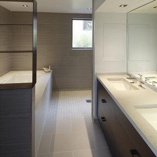 Imagen de cuarto de baño principal, minimalista, con lavabo bajoencimera, armarios con paneles lisos, puertas de armario de madera en tonos medios, ducha abierta, baldosas y/o azulejos beige, baldosas y/o azulejos de cerámica, paredes grises, bañera encastrada sin remate y ducha abierta