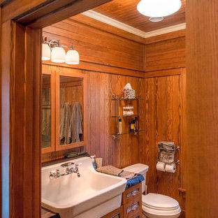 ニューヨークの小さいラスティックスタイルのおしゃれなバスルーム (浴槽なし) (落し込みパネル扉のキャビネット、中間色木目調キャビネット、濃色無垢フローリング、オーバーカウンターシンク、木製洗面台、茶色い床) の写真