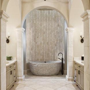 Modelo de cuarto de baño principal, mediterráneo, extra grande, con armarios con paneles empotrados, puertas de armario beige, bañera exenta, baldosas y/o azulejos beige, paredes beige, ducha empotrada, baldosas y/o azulejos de piedra, suelo de travertino y suelo beige