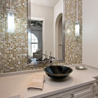 Bathroom - mid-sized mediterranean bathroom idea in Houston with recessed-panel cabinets, gray cabinets, beige walls, a vessel sink and solid surface countertops