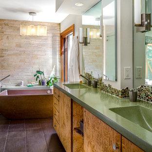 Großes Modernes Badezimmer En Suite mit flächenbündigen Schrankfronten, hellen Holzschränken, freistehender Badewanne, Duschnische, Toilette mit Aufsatzspülkasten, grünen Fliesen, Fliesen aus Glasscheiben, beiger Wandfarbe, Porzellan-Bodenfliesen, integriertem Waschbecken und Beton-Waschbecken/Waschtisch in Sonstige