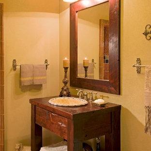 Diseño de cuarto de baño con ducha, de estilo americano, de tamaño medio, con lavabo encastrado, armarios tipo mueble, puertas de armario con efecto envejecido, encimera de madera, baldosas y/o azulejos de terracota, paredes amarillas, suelo de baldosas de terracota, bañera encastrada, ducha empotrada y sanitario de dos piezas