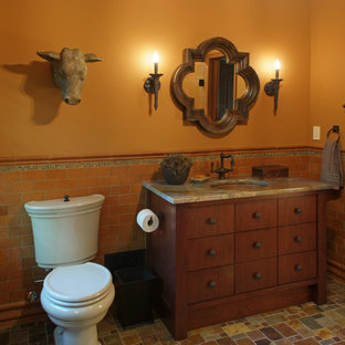 Cette image montre une salle d'eau sud-ouest américain de taille moyenne avec un lavabo encastré, un placard en trompe-l'oeil, des portes de placard en bois brun, une baignoire encastrée, une douche à l'italienne, un WC séparé, un carrelage multicolore, des carreaux en terre cuite, un mur orange et un sol en carreau de terre cuite.