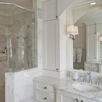 Corner shower - traditional white tile corner shower idea in Charlotte with an undermount sink, recessed-panel cabinets and white cabinets