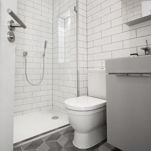 Immagine di una piccola stanza da bagno design con ante grigie, doccia doppia, piastrelle nere, piastrelle in ceramica, pareti bianche, pavimento con piastrelle in ceramica, WC a due pezzi e lavabo a consolle