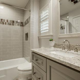 ダラスの中サイズのトラディショナルスタイルのおしゃれなバスルーム (浴槽なし) (レイズドパネル扉のキャビネット、グレーのキャビネット、アルコーブ型浴槽、シャワー付き浴槽、一体型トイレ、ベージュのタイル、セラミックタイル、ベージュの壁、アンダーカウンター洗面器、珪岩の洗面台、シャワーカーテン) の写真