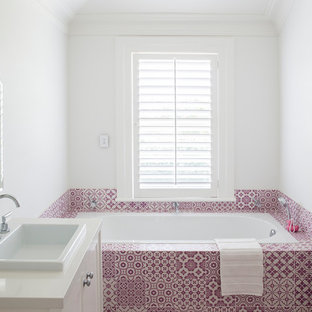 Ejemplo de cuarto de baño principal, mediterráneo, de tamaño medio, con lavabo encastrado, puertas de armario blancas, bañera empotrada, paredes blancas y baldosas y/o azulejos rosa