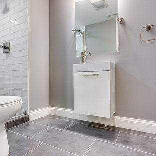 Immagine di una piccola stanza da bagno con doccia tradizionale con ante lisce, ante bianche, doccia alcova, WC a due pezzi, piastrelle grigie, piastrelle di vetro, pareti beige, pavimento in cementine, lavabo integrato, top in superficie solida, pavimento grigio e porta doccia scorrevole