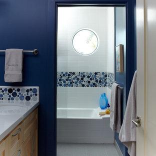 Foto de cuarto de baño costero, pequeño, con lavabo bajoencimera, armarios con paneles empotrados, puertas de armario de madera clara, sanitario de dos piezas, baldosas y/o azulejos azules, baldosas y/o azulejos de vidrio, paredes azules y suelo de baldosas de porcelana