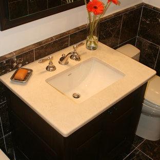 ニューヨークの小さいトランジショナルスタイルのおしゃれなマスターバスルーム (アンダーカウンター洗面器、家具調キャビネット、濃色木目調キャビネット、大理石の洗面台、シャワー付き浴槽、一体型トイレ、茶色いタイル、石タイル、茶色い壁、大理石の床、アルコーブ型浴槽、茶色い床、オープンシャワー、ベージュのカウンター、ニッチ、洗面台1つ、独立型洗面台、三角天井) の写真