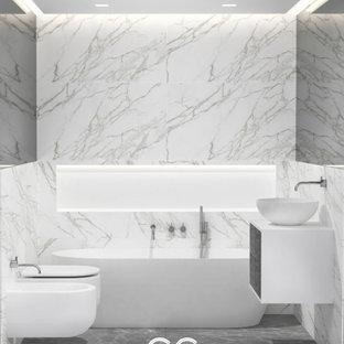 Kleines Modernes Badezimmer En Suite mit flächenbündigen Schrankfronten, grauen Schränken, Whirlpool, Duschbadewanne, Wandtoilette mit Spülkasten, weißen Fliesen, Marmorfliesen, weißer Wandfarbe, Marmorboden, Waschtischkonsole, Waschtisch aus Holz, grauem Boden, weißer Waschtischplatte, Nische, Einzelwaschbecken, schwebendem Waschtisch und Holzdielendecke in London