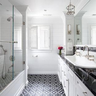 Modelo de cuarto de baño principal, clásico renovado, con armarios estilo shaker, puertas de armario blancas, paredes blancas, suelo con mosaicos de baldosas, lavabo encastrado, suelo negro, ducha con puerta corredera, encimeras negras y combinación de ducha y bañera
