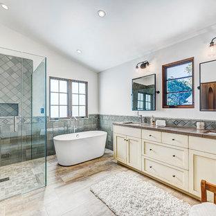 Exempel på ett stort medelhavsstil en-suite badrum, med skåp i shakerstil, skåp i slitet trä, ett fristående badkar, en hörndusch, en toalettstol med separat cisternkåpa, grå kakel, keramikplattor, vita väggar, travertin golv, kaklad bänkskiva, beiget golv och dusch med gångjärnsdörr