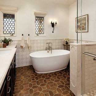 Photo of a small mediterranean ensuite bathroom in Santa Barbara with recessed-panel cabinets, dark wood cabinets, a freestanding bath, an alcove shower, multi-coloured tiles, ceramic tiles, white walls, a submerged sink, solid surface worktops, brown floors, a hinged door and terracotta flooring.