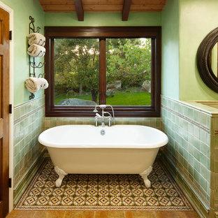 Immagine di una grande stanza da bagno padronale mediterranea con ante con bugna sagomata, ante in legno scuro, vasca con piedi a zampa di leone, piastrelle verdi, piastrelle in ceramica, pareti verdi, pavimento con piastrelle a mosaico, top piastrellato e pavimento multicolore