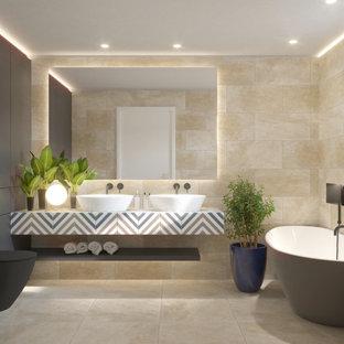 Idéer för mellanstora funkis flerfärgat en-suite badrum, med ett fristående badkar, en dusch/badkar-kombination, vit kakel, keramikplattor, vita väggar, en vägghängd toalettstol, cementgolv, ett piedestal handfat, kaklad bänkskiva och beiget golv