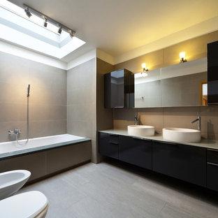 Источник вдохновения для домашнего уюта: большая главная ванная комната в стиле модернизм с настольной раковиной, плоскими фасадами, серыми фасадами, стеклянной столешницей, полновстраиваемой ванной, душем над ванной, раздельным унитазом, серой плиткой, керамогранитной плиткой, серыми стенами и полом из керамогранита