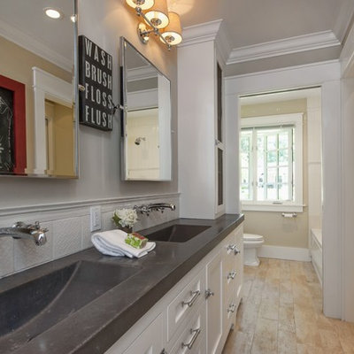 Elegant beige tile and white tile bathroom photo in San Francisco with an integrated sink, white cabinets and concrete countertops
