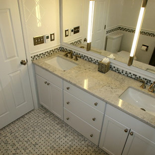 Mid-sized transitional master white tile and ceramic tile marble floor, multicolored floor, double-sink and vaulted ceiling bathroom photo in New York with recessed-panel cabinets, white cabinets, a two-piece toilet, white walls, an undermount sink, quartz countertops, a hinged shower door, gray countertops and a built-in vanity