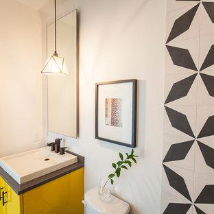 Kleines Modernes Duschbad mit flächenbündigen Schrankfronten, gelben Schränken, Wandtoilette mit Spülkasten, schwarz-weißen Fliesen, Keramikfliesen, weißer Wandfarbe, Betonboden, Waschtischkonsole und Quarzwerkstein-Waschtisch in Austin