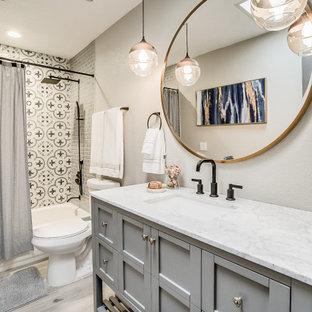 フェニックスのトランジショナルスタイルのおしゃれな浴室 (シェーカースタイル扉のキャビネット、グレーのキャビネット、アルコーブ型浴槽、シャワー付き浴槽、グレーの壁、木目調タイルの床、アンダーカウンター洗面器、グレーの床、シャワーカーテン、白い洗面カウンター、洗面台1つ、独立型洗面台) の写真