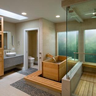 Trendy pebble tile floor japanese bathtub photo in Los Angeles with a vessel sink
