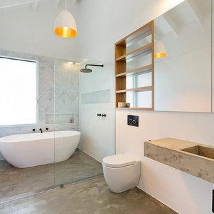 Esempio di una stanza da bagno con doccia minimal con vasca freestanding, zona vasca/doccia separata, WC sospeso, piastrelle grigie, piastrelle bianche, pareti bianche, pavimento in cemento, lavabo sospeso, top in cemento, pavimento grigio, doccia aperta e top grigio