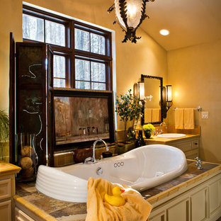 Example of a large tuscan master bathroom design in Other with an undermount tub, yellow walls, beaded inset cabinets and yellow cabinets