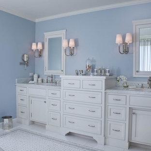 Modelo de cuarto de baño principal, tradicional, grande, con armarios estilo shaker, puertas de armario blancas, bañera exenta, ducha empotrada, paredes azules, suelo de linóleo, lavabo bajoencimera, encimera de mármol, baldosas y/o azulejos blancos, baldosas y/o azulejos de mármol, suelo blanco y ducha con puerta con bisagras