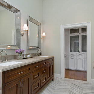 This is an example of a large traditional master bathroom in San Francisco with beaded inset cabinets, medium wood cabinets, a hinged shower door, an undermount tub, a corner shower, gray tile, ceramic tile, beige walls, vinyl floors, an undermount sink, stainless steel benchtops and grey floor.